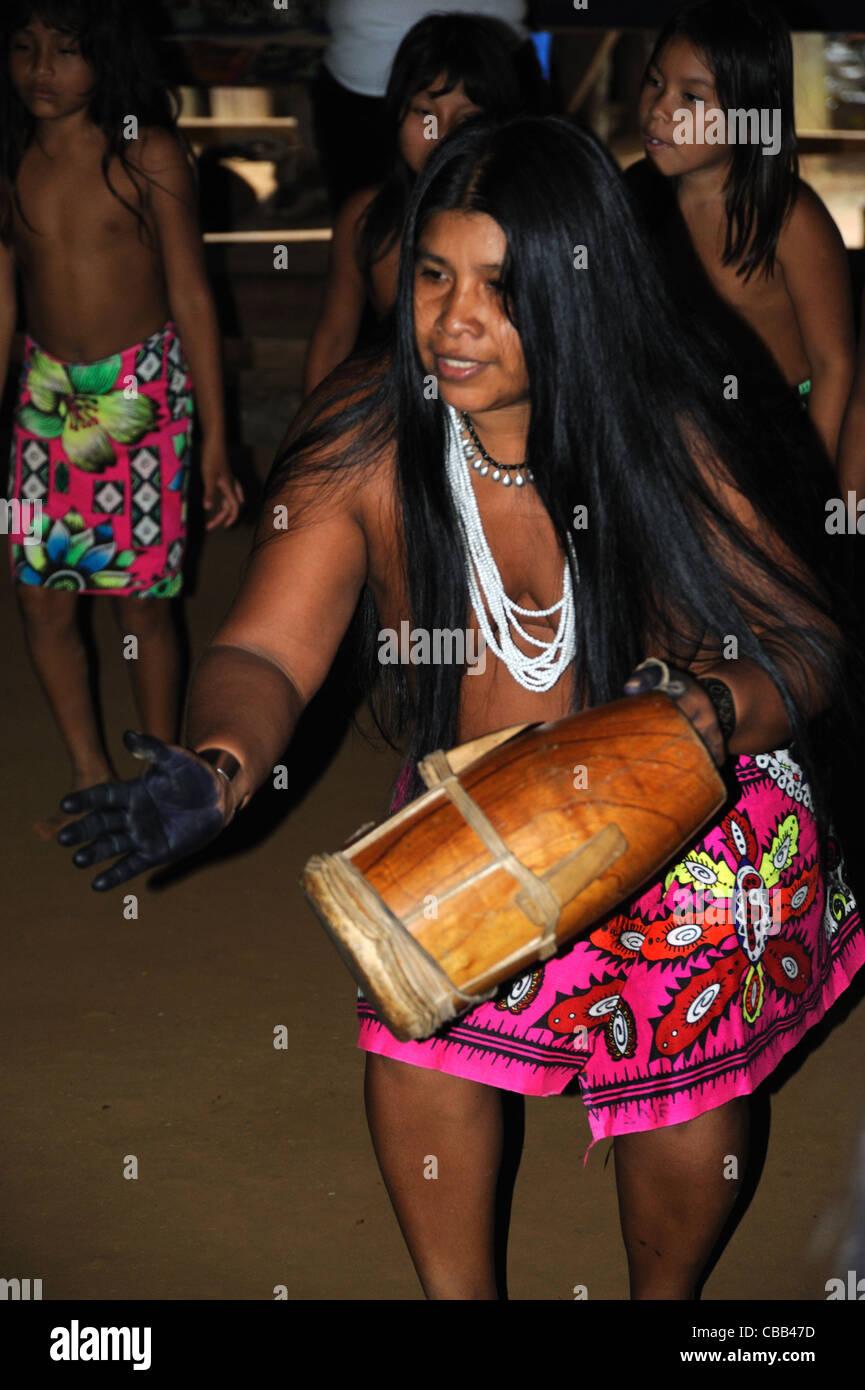 Mujer indígena Embera drumming y bailando en la comunidad indígena Embera Puru en Panamá. Foto de stock