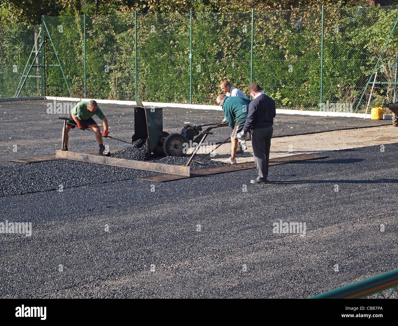 Construcción de canchas de tenis de arcilla sintética - la base de la capa de Macadam está nivelado Imagen De Stock