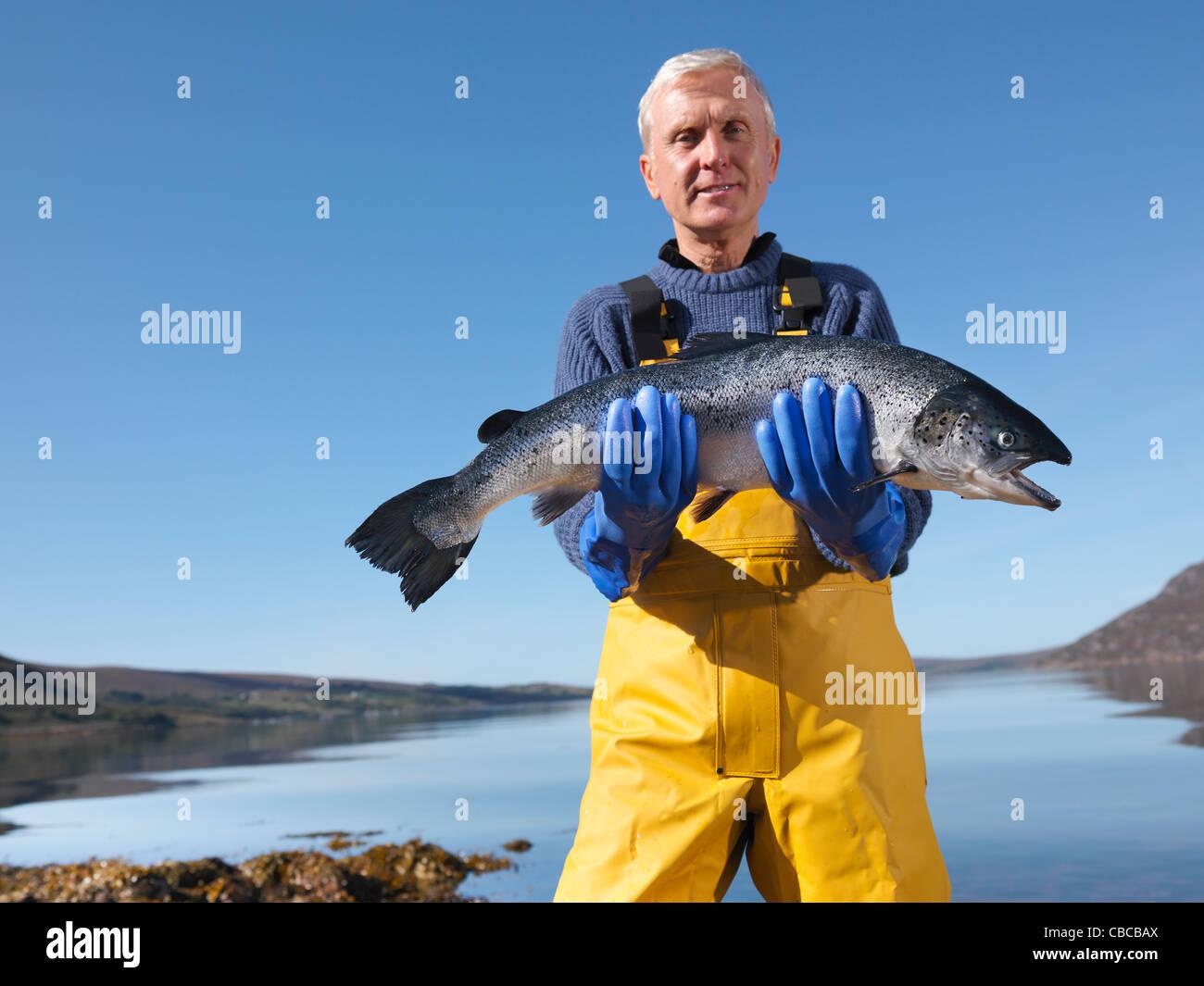 Pescador sosteniendo el salmón por el lago Imagen De Stock