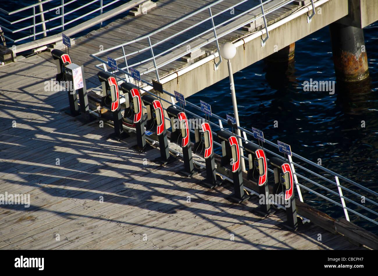 Línea de teléfonos rojos para llamadas internacionales en el muelle de cruceros Imagen De Stock