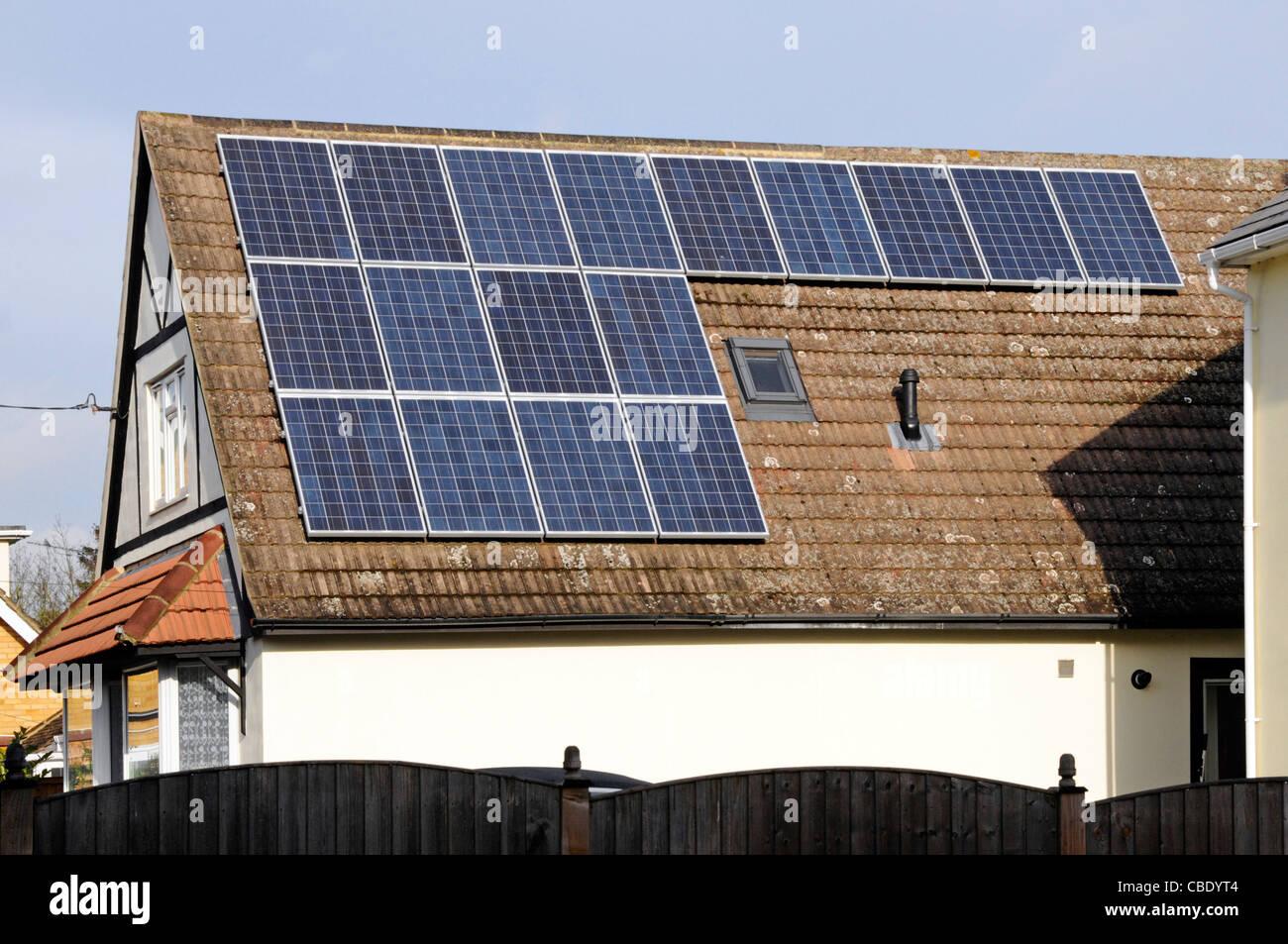 Paneles solares en sunshine instalado en el techo mirando al sur en el soleado cielo azul día casa unifamiliar Imagen De Stock