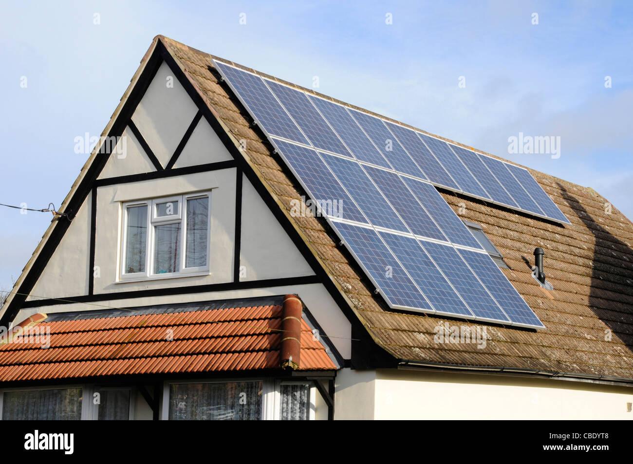 Los paneles solares instalados en el techo de la casa unifamiliar junto a un rooflight existente Imagen De Stock