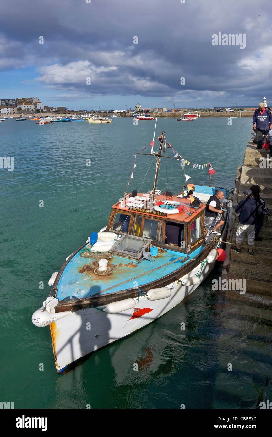 Los turistas que salen de viaje en barco de verano en Old Harbour, St Ives, Cornwall, en el suroeste de Inglaterra, Imagen De Stock