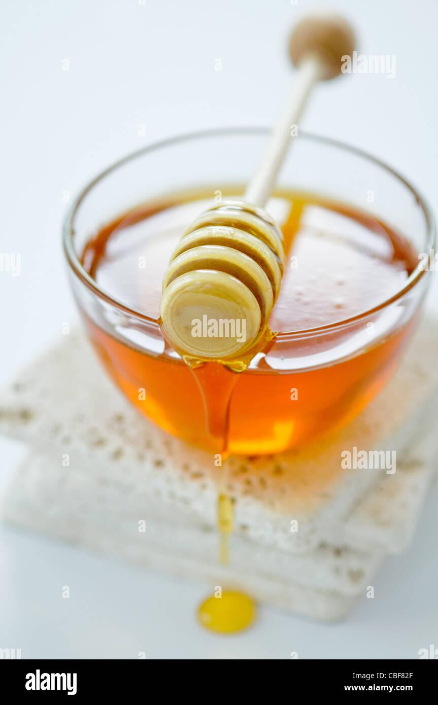 Recipiente de goteo con miel miel penetrador Foto de stock