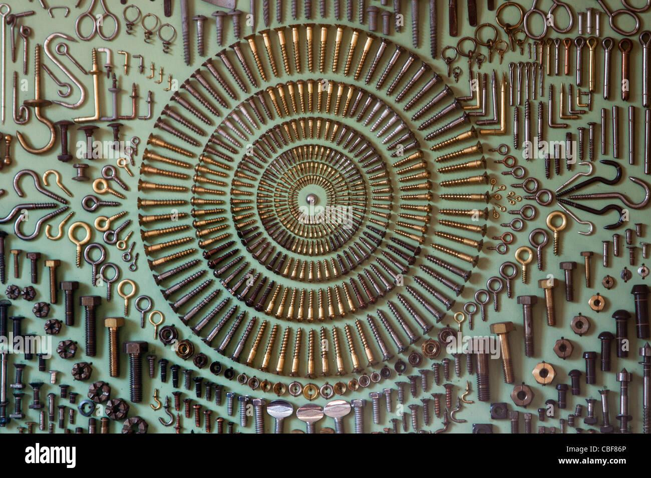 Tornillos ganchos ojos remaches de tuercas y pernos montados en un patrón regular en la placa de la pantalla Imagen De Stock