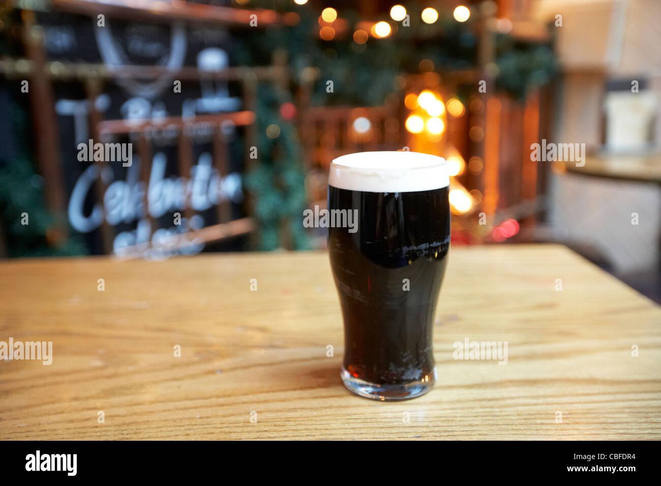 Pinta de cerveza negra sobre una tabla en un gastro pub Londres England Reino Unido Imagen De Stock