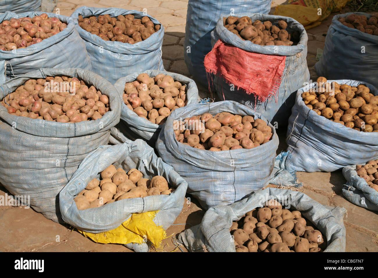 Patatas para la venta en grandes bolsas en mercado en Challapata, Altiplano, Bolivia Foto de stock