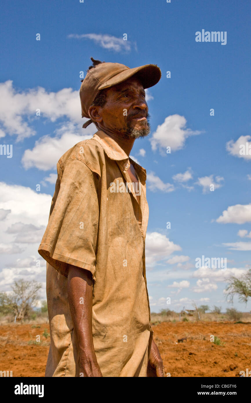 Agricultor keniano mirando por encima de su desnudo en campos de tierra roja Sagalla cerca de VDI en el sur de Kenya Imagen De Stock