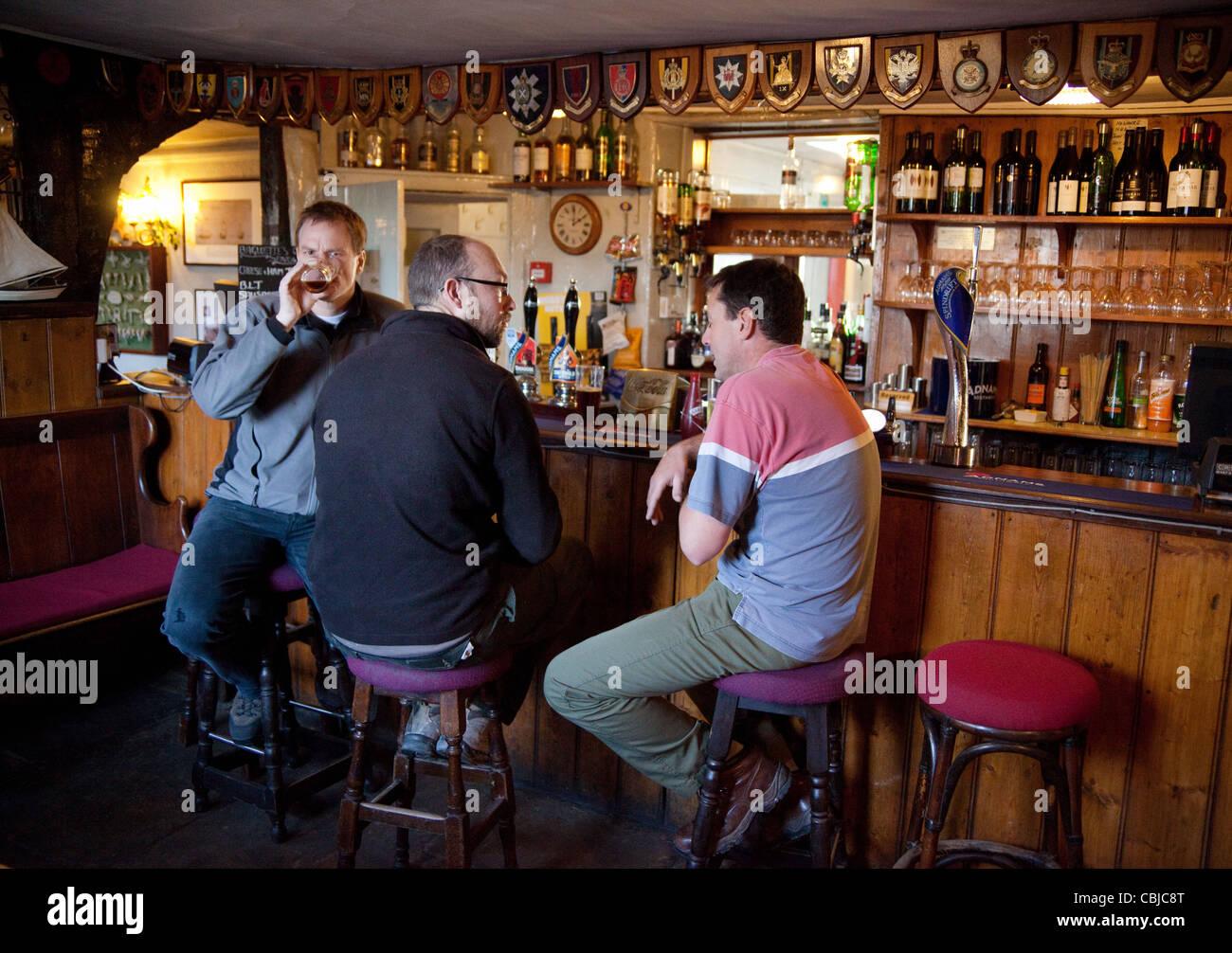 Tres hombres bebiendo y charlando en un bar, el pub Jolly Sailor, aldea Orford Suffolk UK Foto de stock