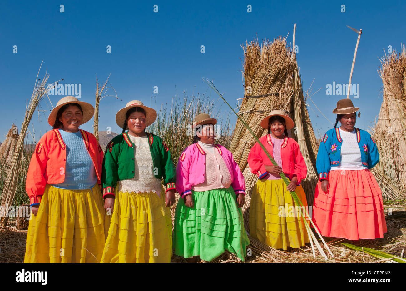 Lago Titicaca Perú con mujeres locales tradicionales de la historia de la tribu de Uros en coloridas ropas Imagen De Stock