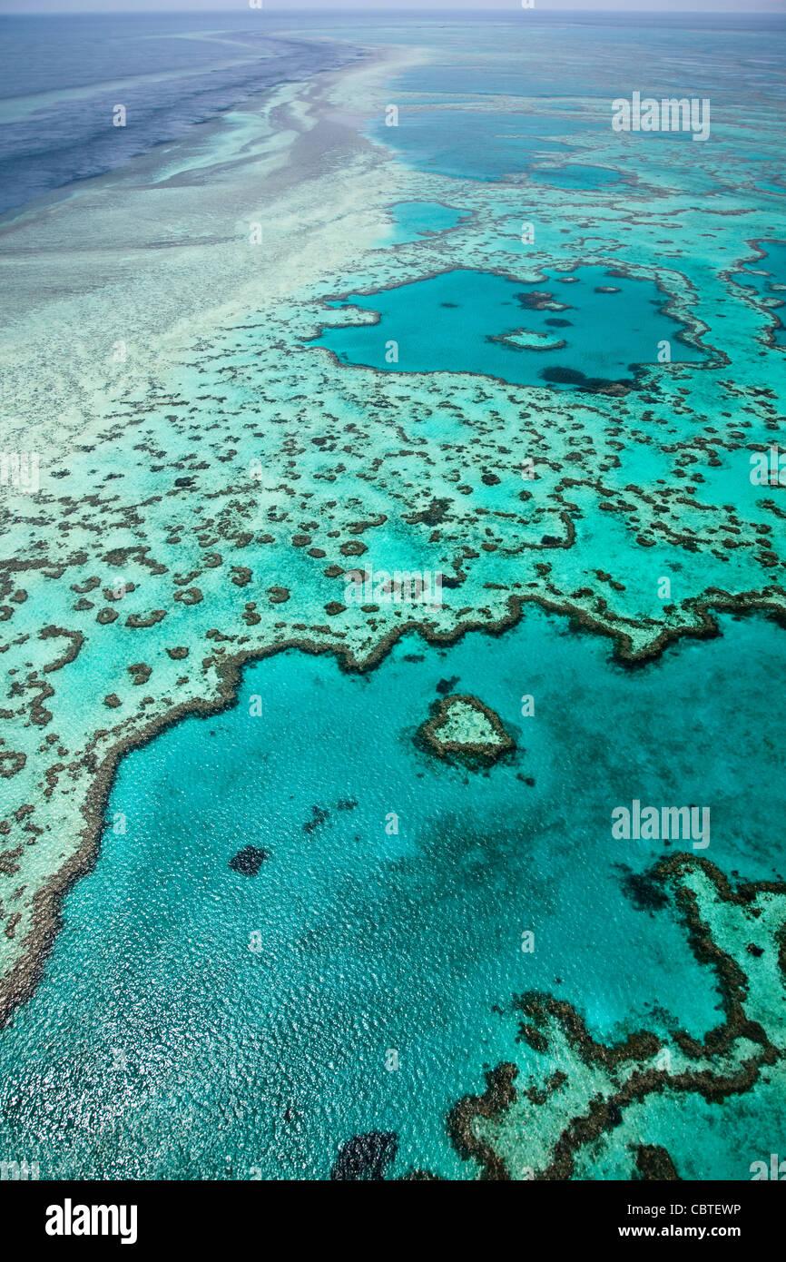 Hermosas vistas aéreas de corazón en el espectacular arrecife de la Gran Barrera de Coral, cerca de las islas Whitsunday de Queensland, Australia. Foto de stock