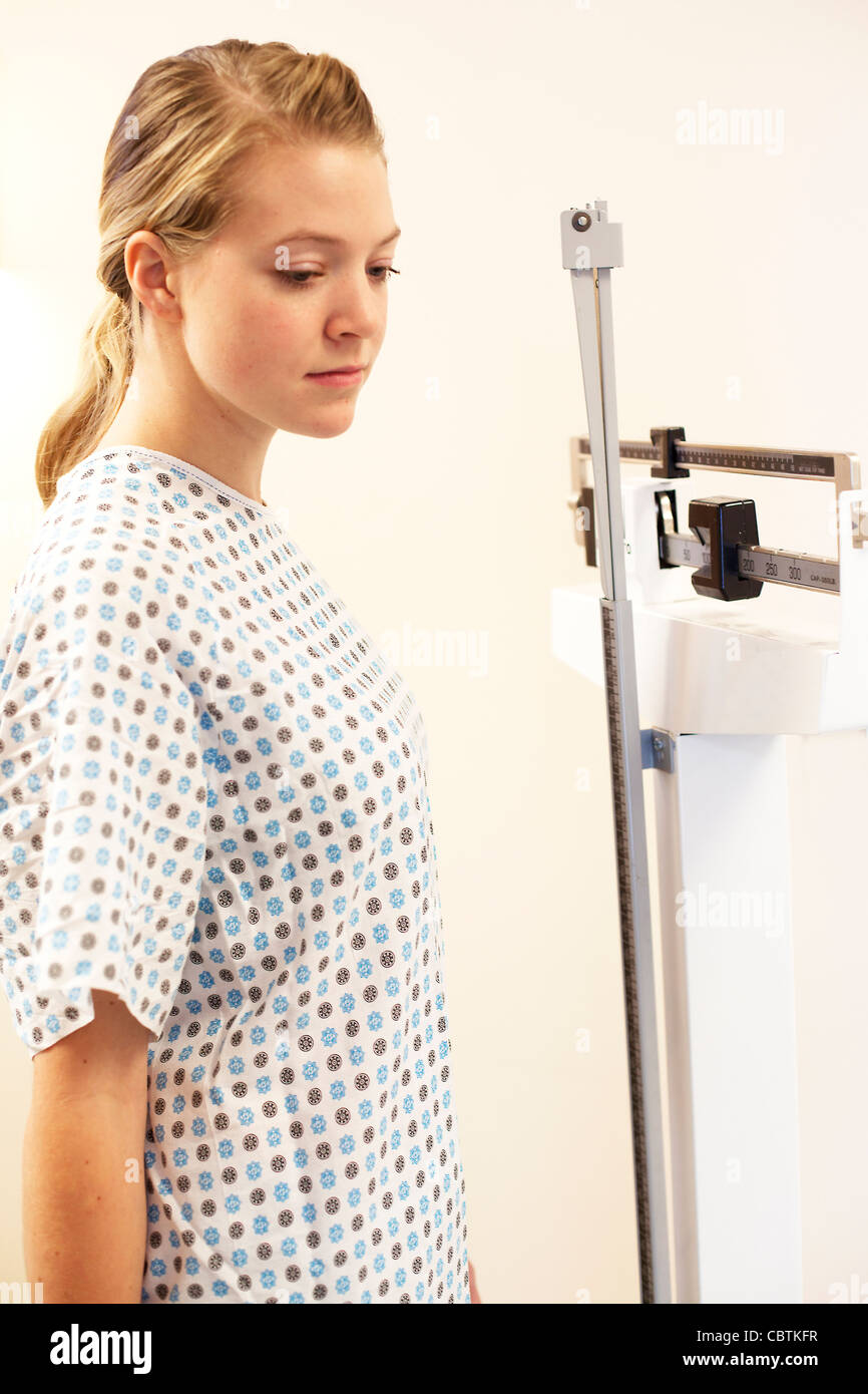 Mujer joven misma ponderación en consultorio médico escala. Imagen De Stock