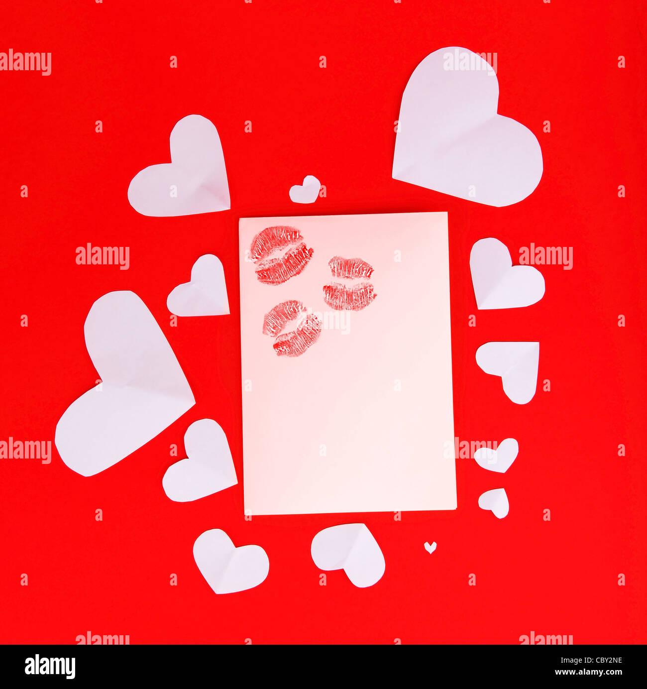 Tarjeta en blanco con rojo besos aislado sobre fondo rojo, imagen conceptual del amor y el día de San Valentín Imagen De Stock