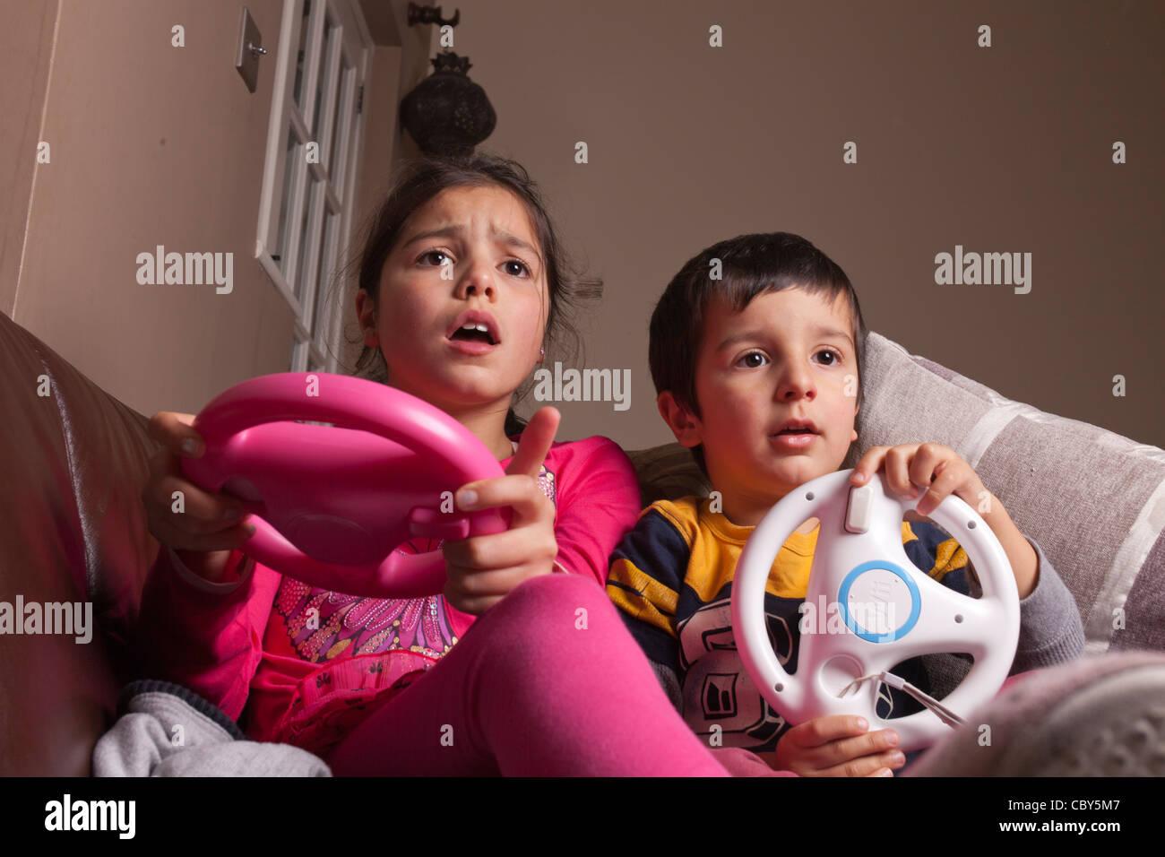 Hermanos jugando juego de ordenador en casa Imagen De Stock