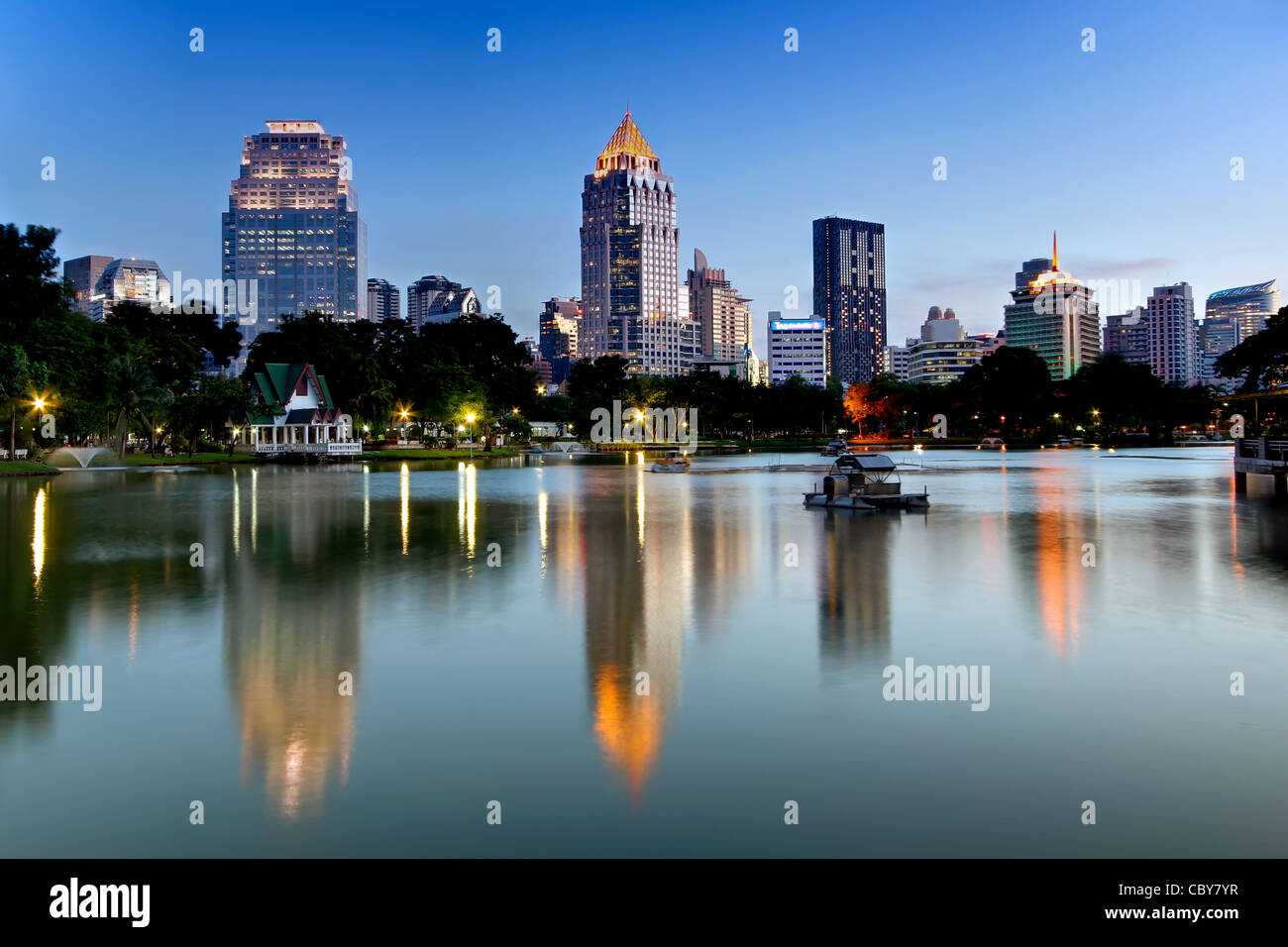 Vista hacia la calle Silom y Rama IV Road del Parque Lumpini al anochecer, Bangkok. Imagen De Stock