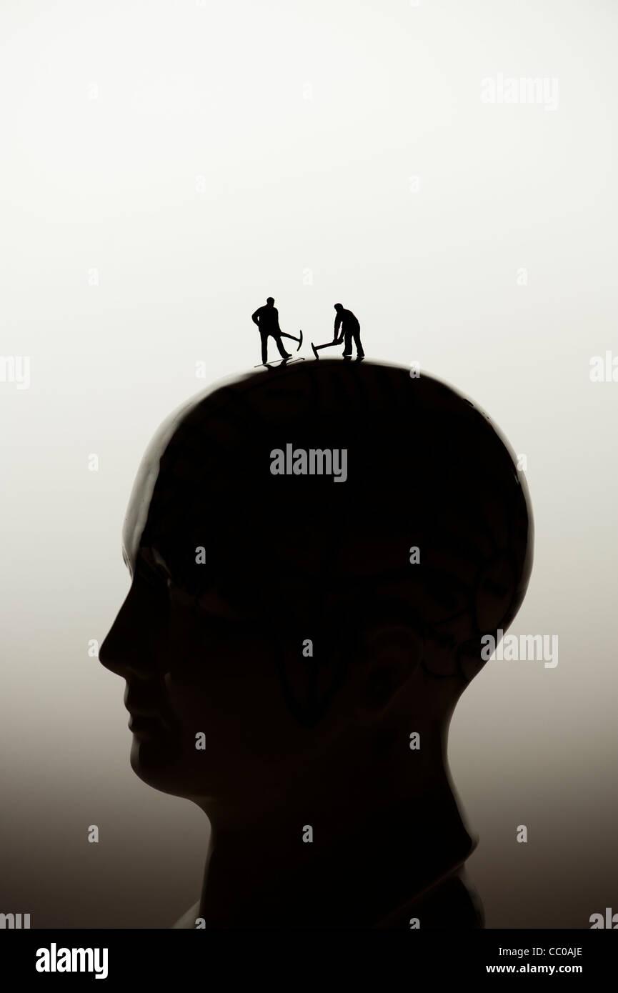 Elige a tu cerebro, una cirugía cerebral, concepto Conceptual - pequeñas figuras cavando en una cabeza Imagen De Stock