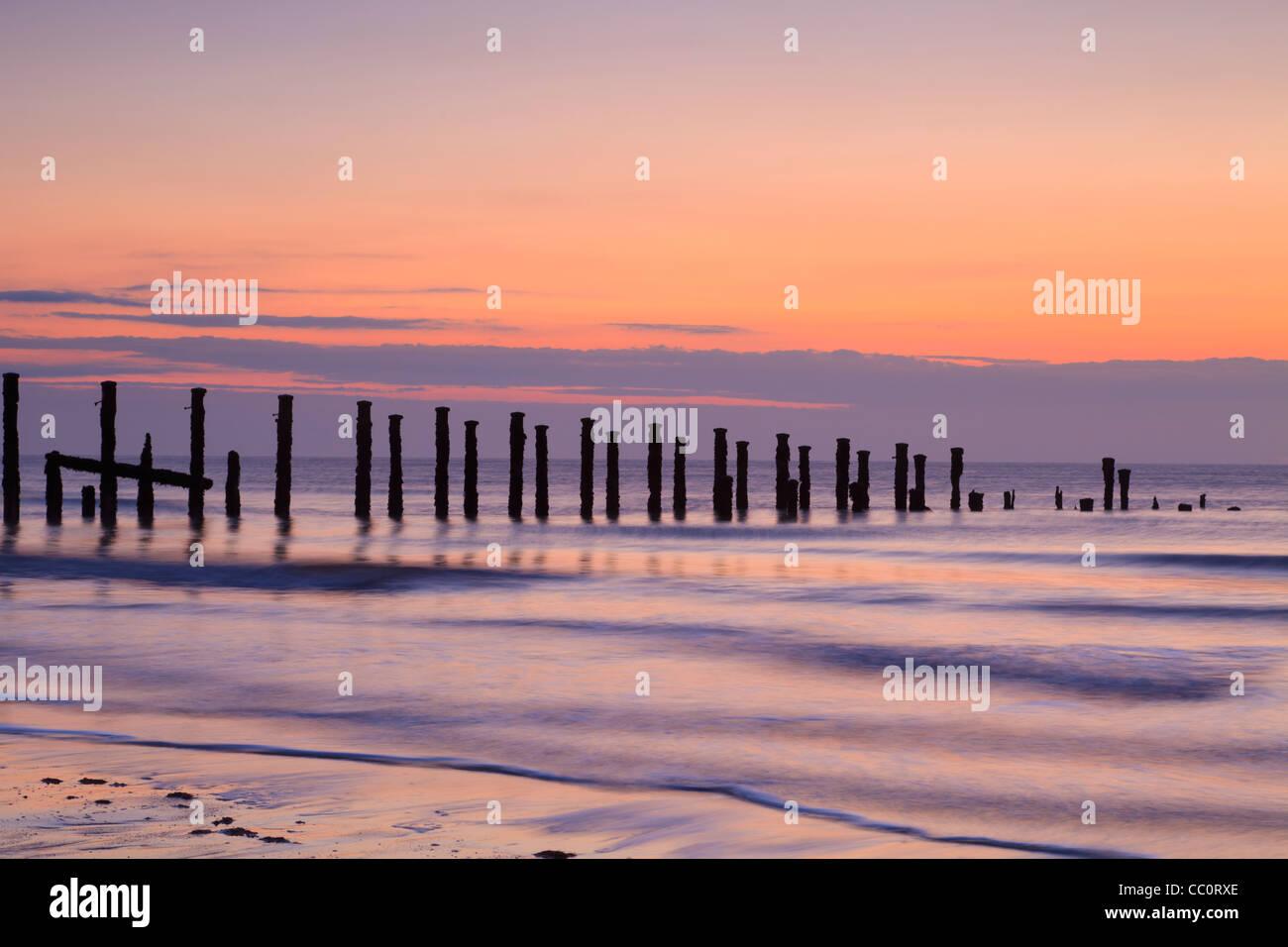 Viejas defensas contra el mar al amanecer, el agua suave de la larga exposición. Imagen De Stock