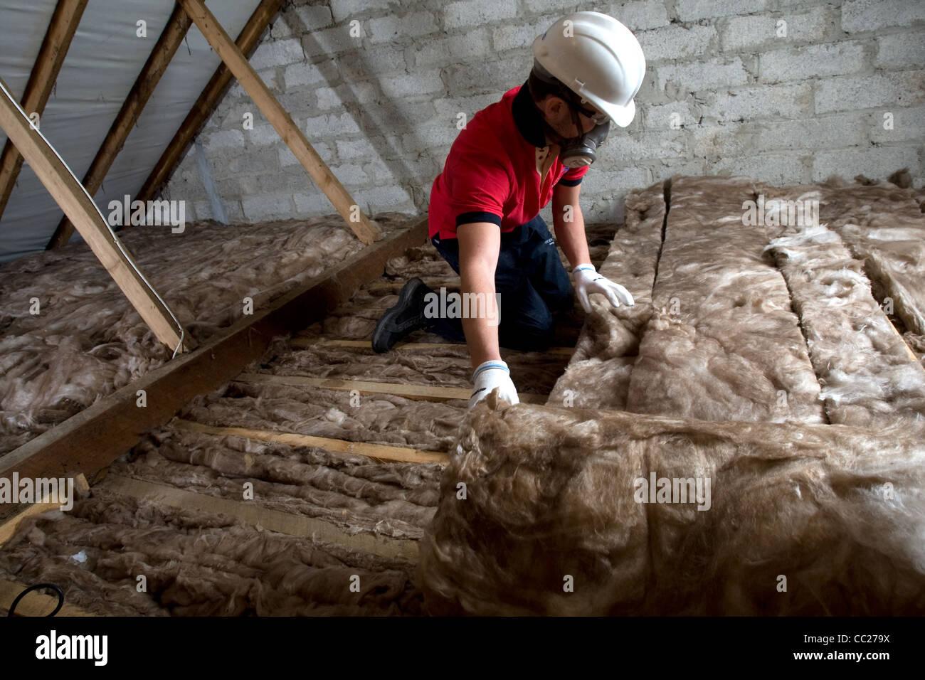 Un trabajador establece loft aislamiento en el ático de una propiedad residencial Imagen De Stock