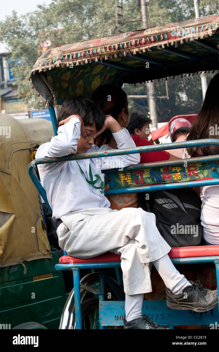 Cansado colegial yendo a casa en un rickshaw, Vieja Delhi, India Imagen De Stock
