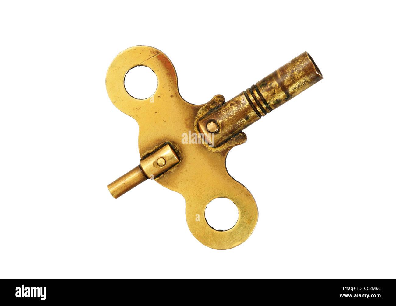 Latón Antiguo reloj clave de bobinado aislado sobre fondo blanco. Imagen De Stock