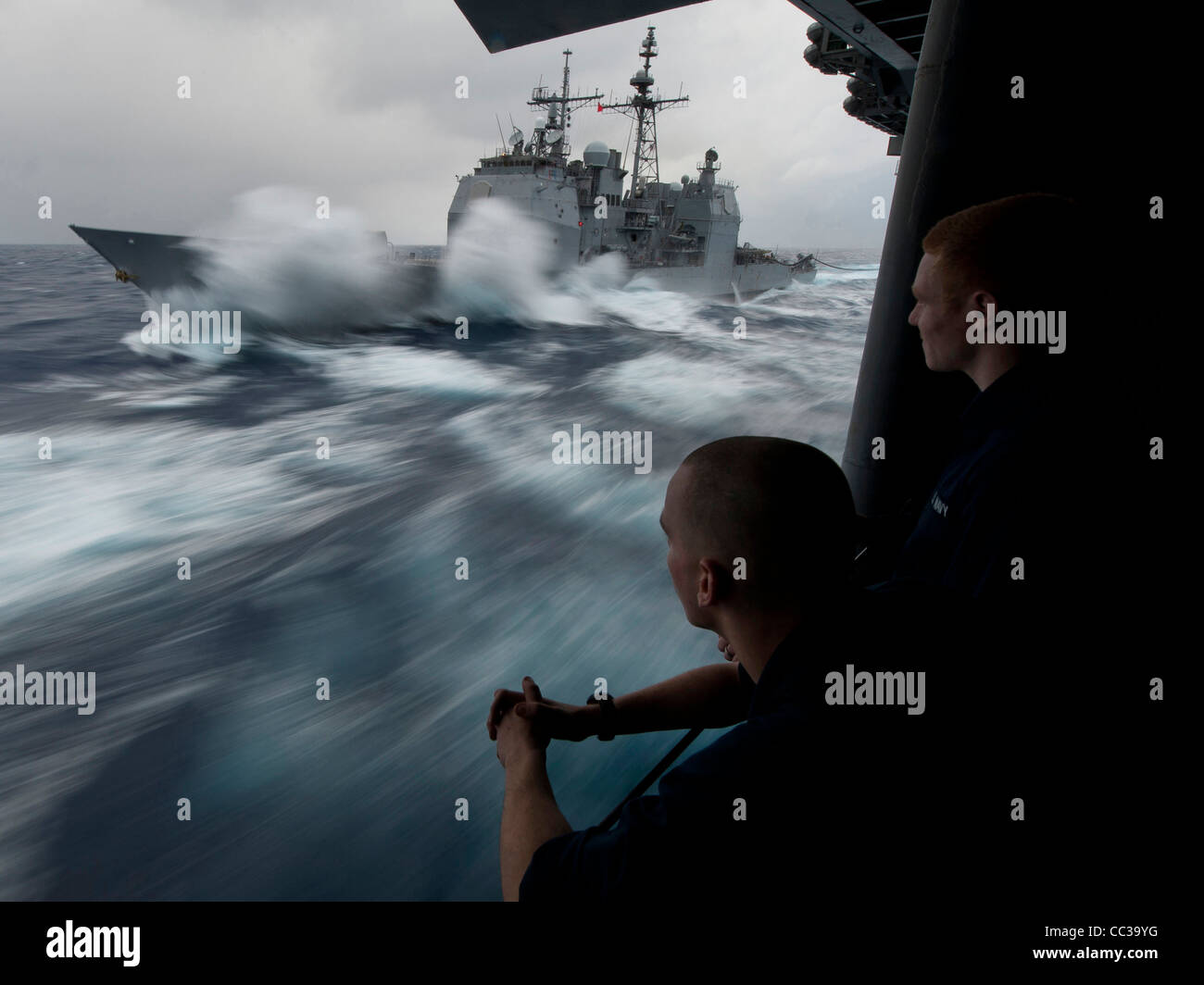 Guiado de clase Ticonderoga-crucero de misiles USS Bunker Hill (CG 52) tomar combustible en mar gruesa durante un Foto de stock