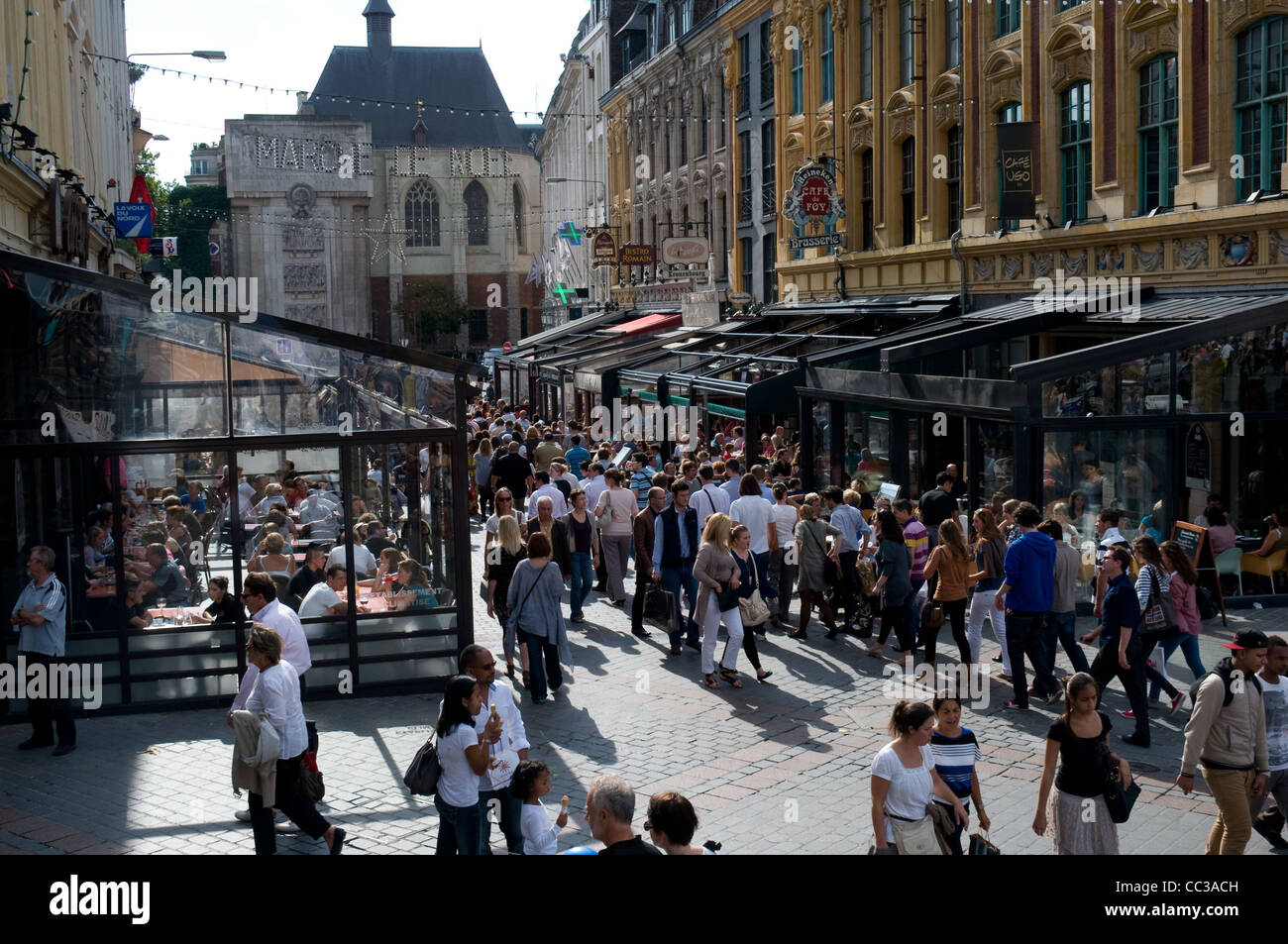 Los turistas y lugareños pasan a lo largo de Pl. Rihour, Lille, Francia busca en los restaurantes y cafeterías. Imagen De Stock