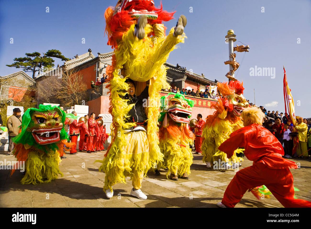 Las personas que llevan a cabo la danza del león durante la feria, Miaofeng templo Montaña, Beijing, China Imagen De Stock