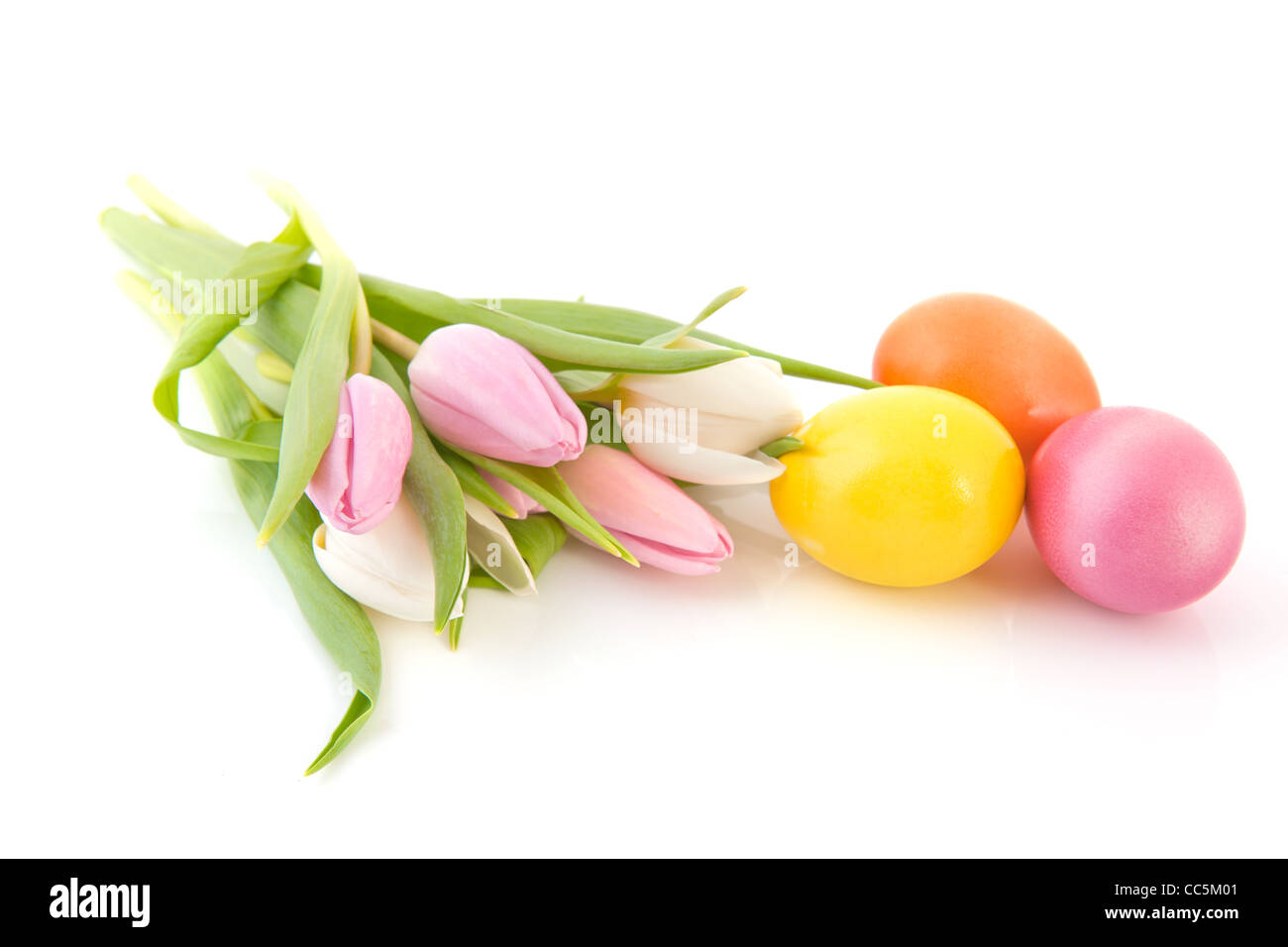 Huevos de pascua de colores pastel y tulipanes Foto de stock