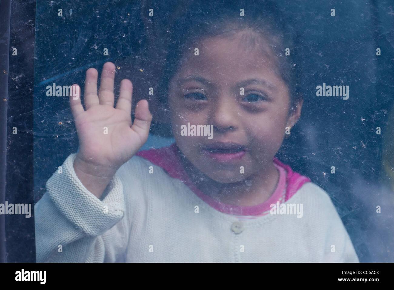 Una niña ecuatoriana niño mirando hacia adelante desde la oscuridad del interior de un coche Imagen De Stock