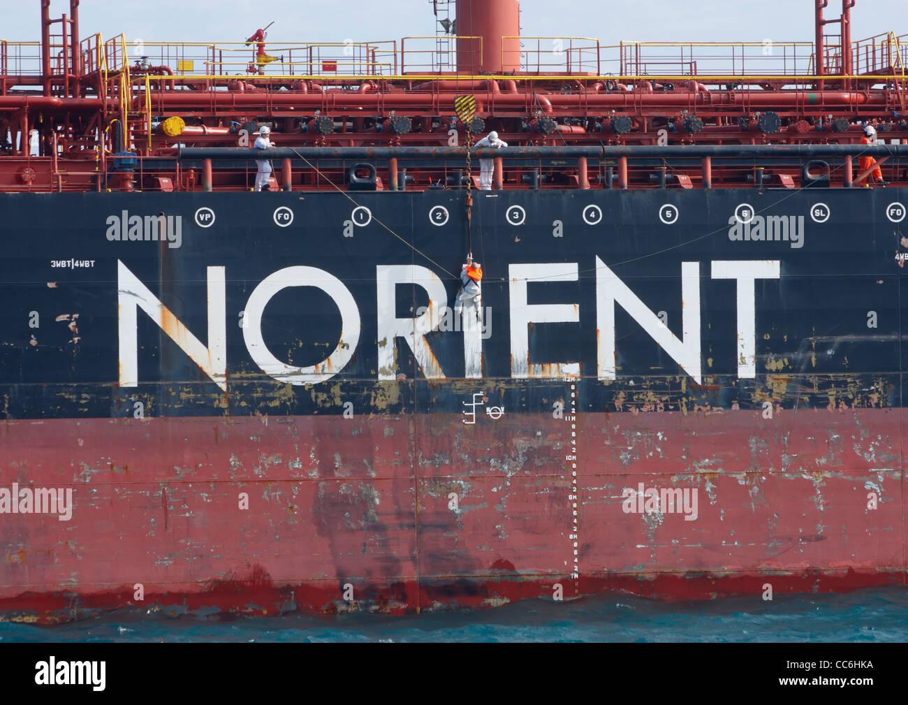 Tripulación colgando de una grúa trabajando en casco del buque petrolero Foto de stock