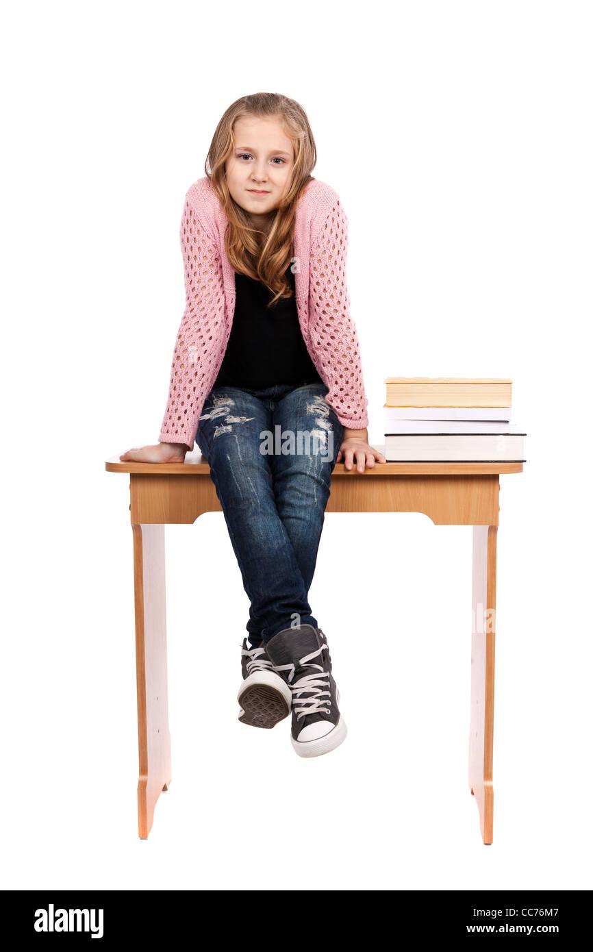 Lindo rubia colegiala sentado en su escritorio con un montón de libros cercano Foto de stock