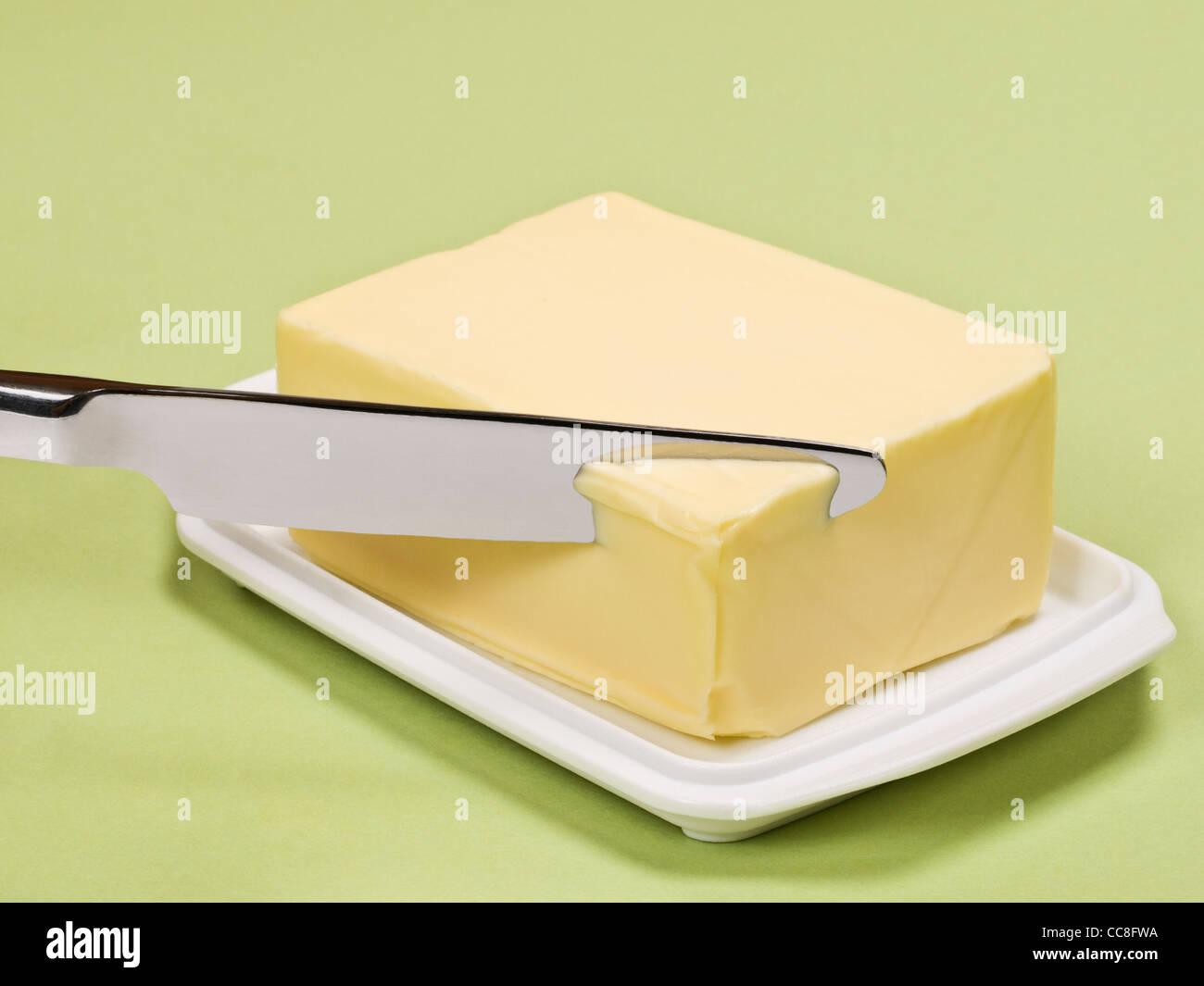 Ein Stück mantequilla wird angeschnitten | un pedazo de mantequilla está cortada Imagen De Stock