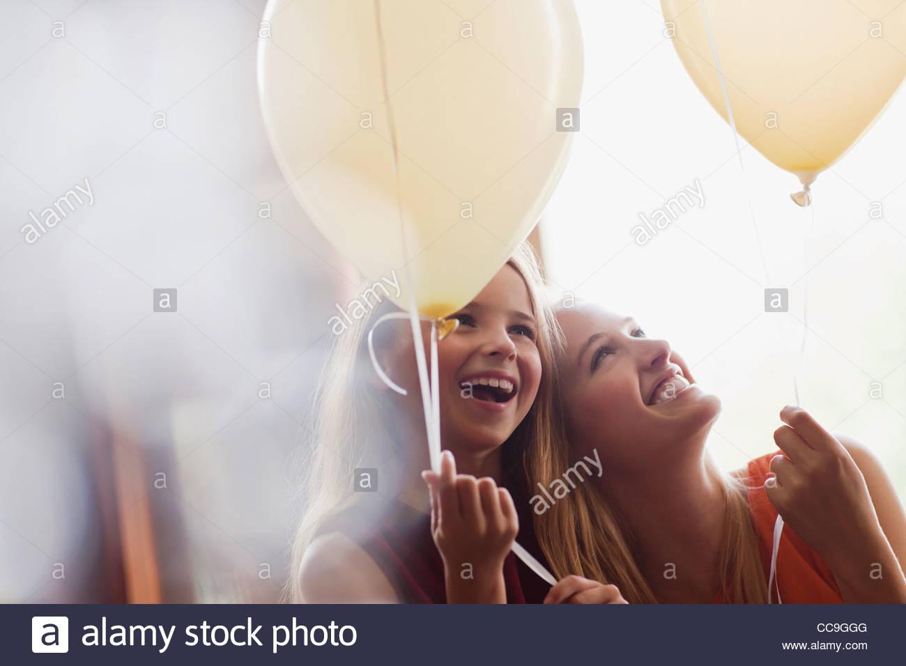 Laughing hermanas con globos Imagen De Stock