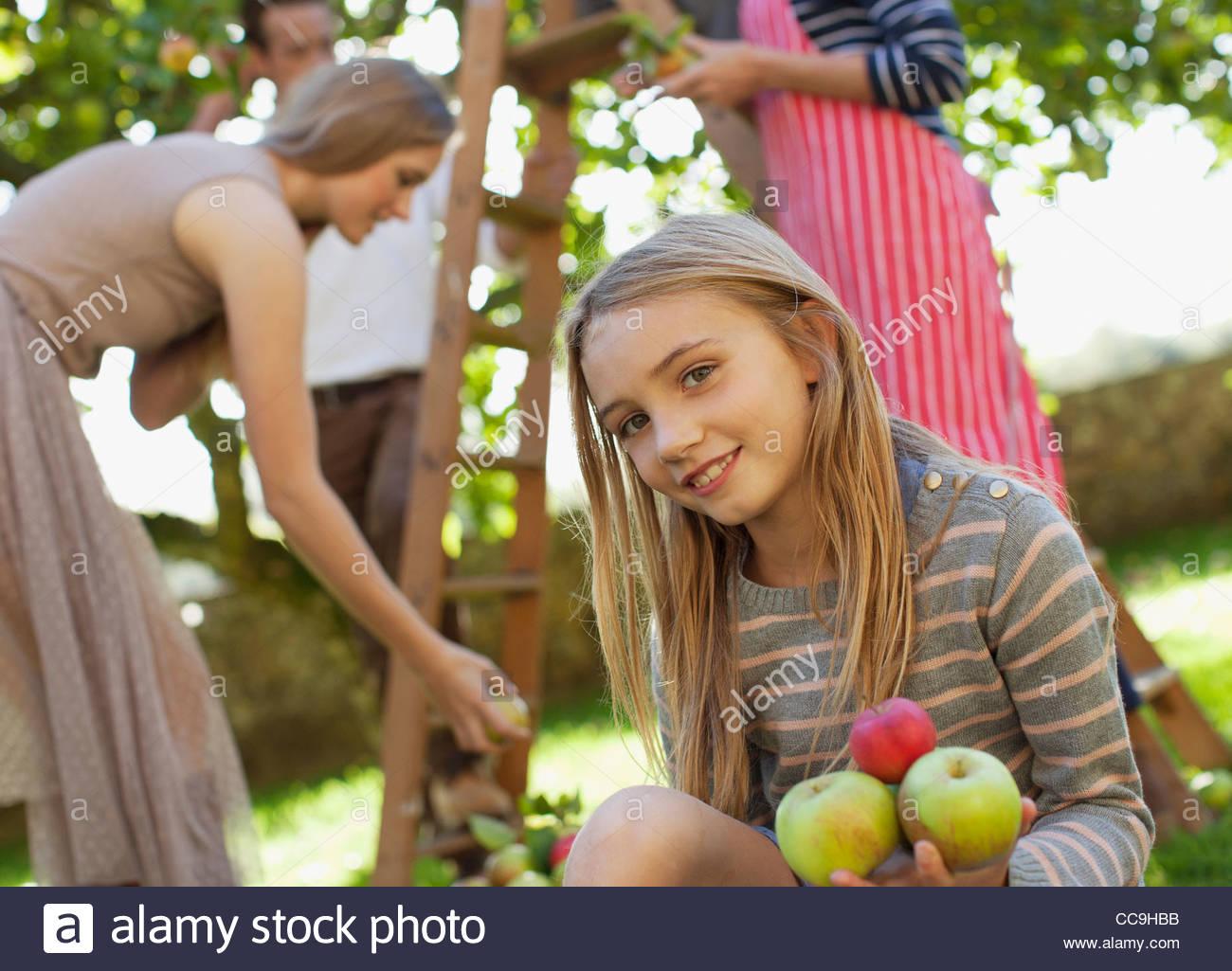 Retrato de niña sonriente sosteniendo las manzanas en huerto Imagen De Stock