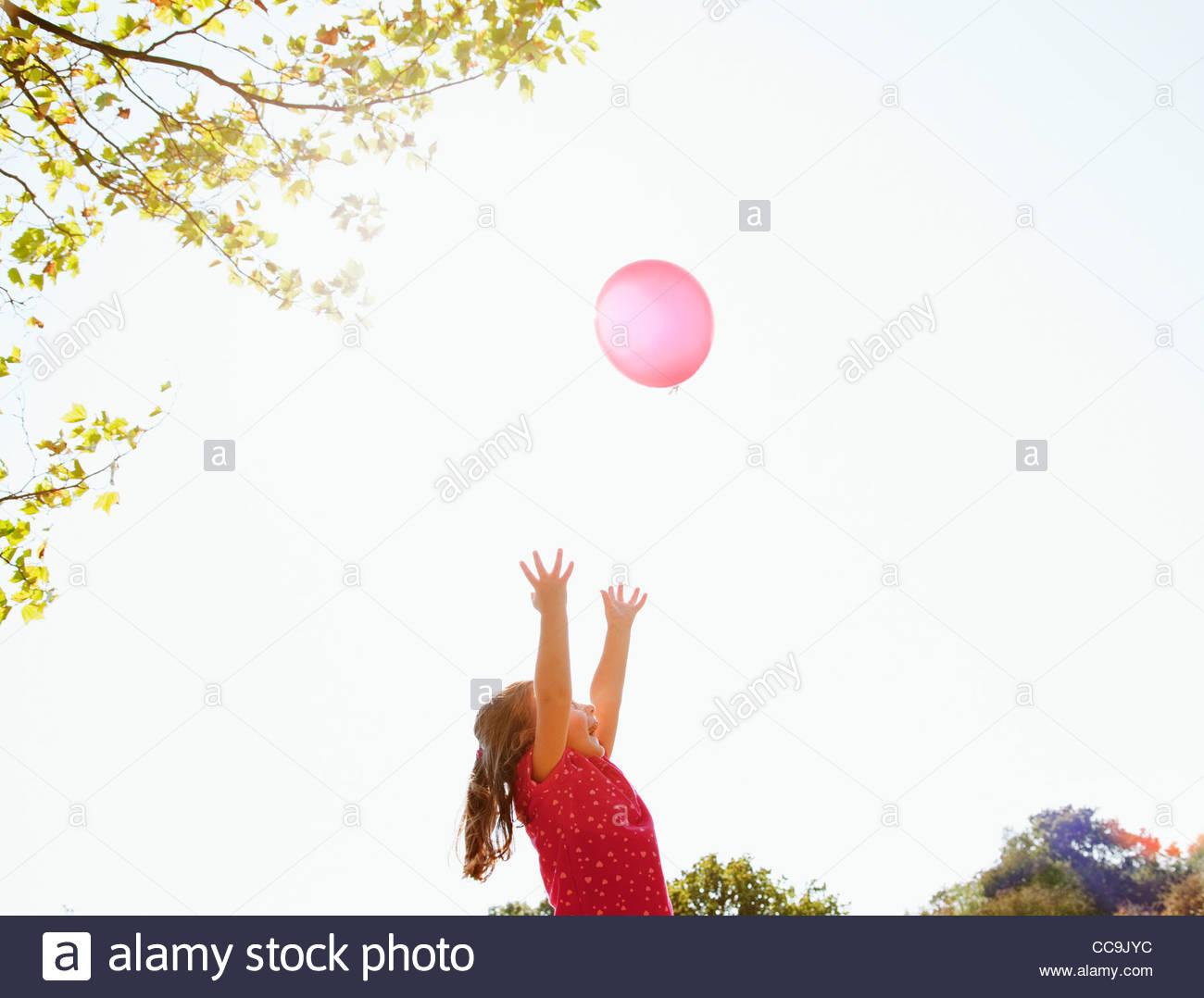 Niña alcanzando globo rojo en el cielo soleado Imagen De Stock