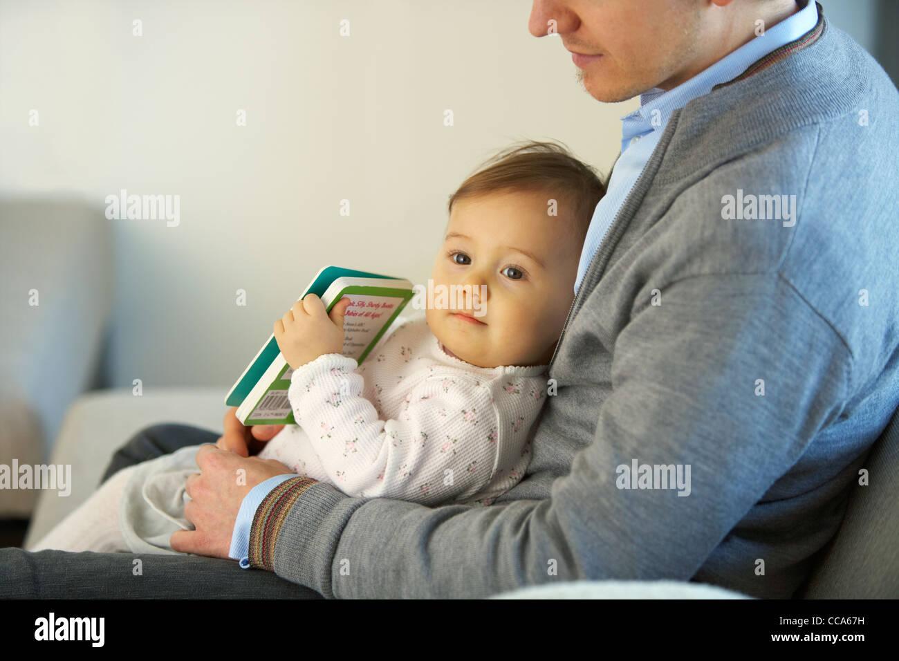 Niña sentada en el Regazo de padre Foto de stock