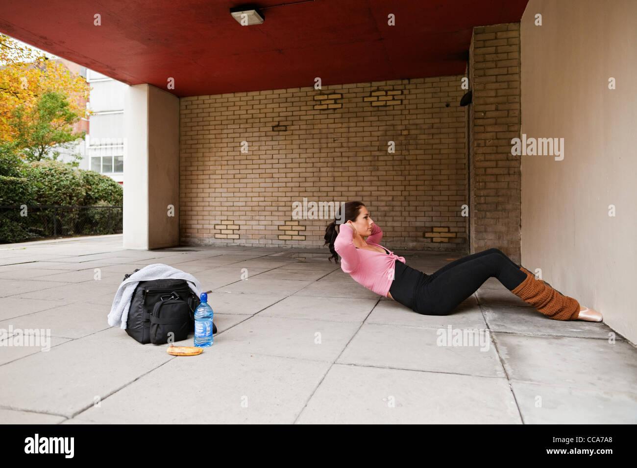 Mujer en calentadores de pierna realizando sentarse ups Imagen De Stock