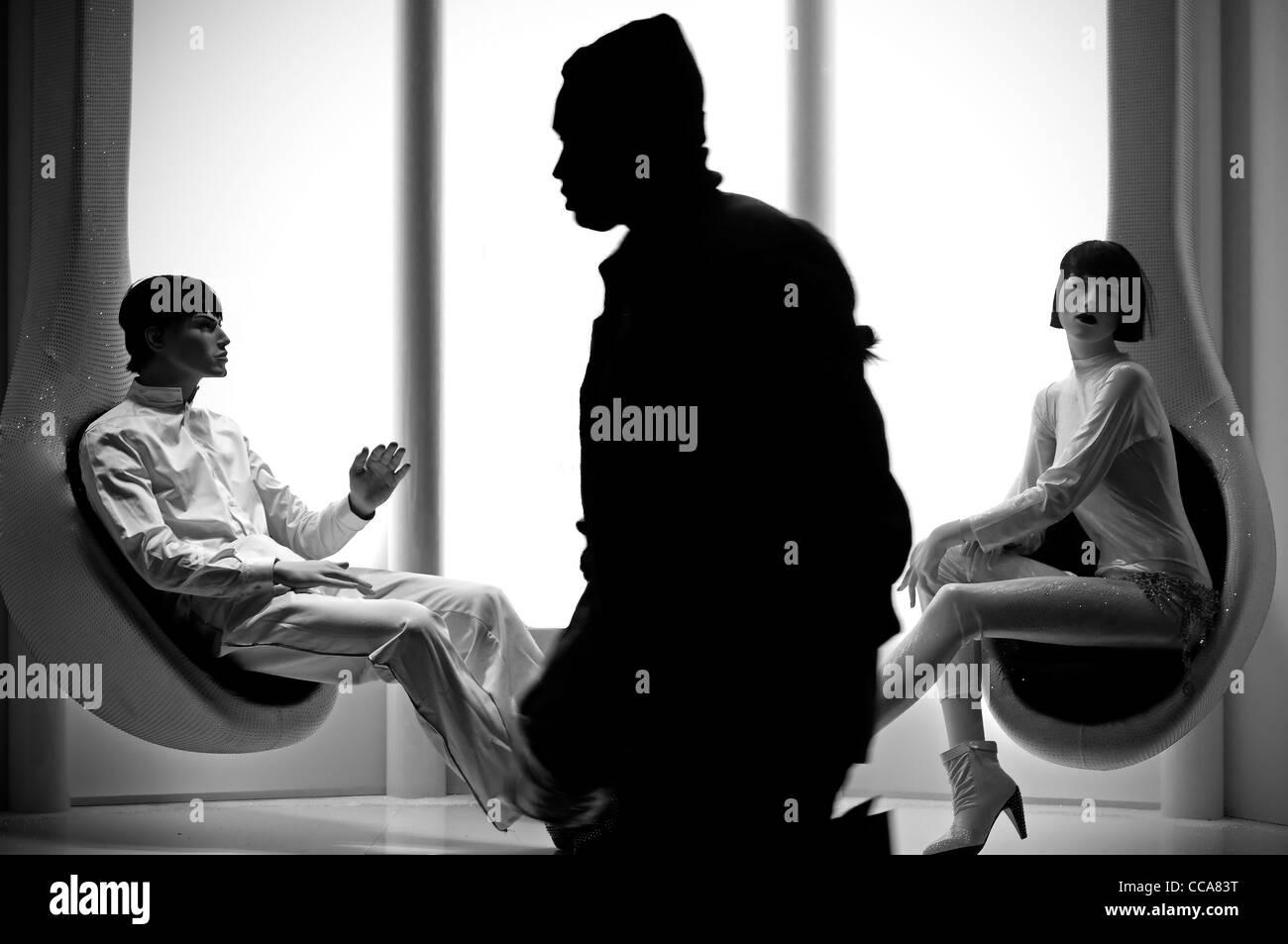 El hombre pasa delante de un escaparate. Imagen De Stock