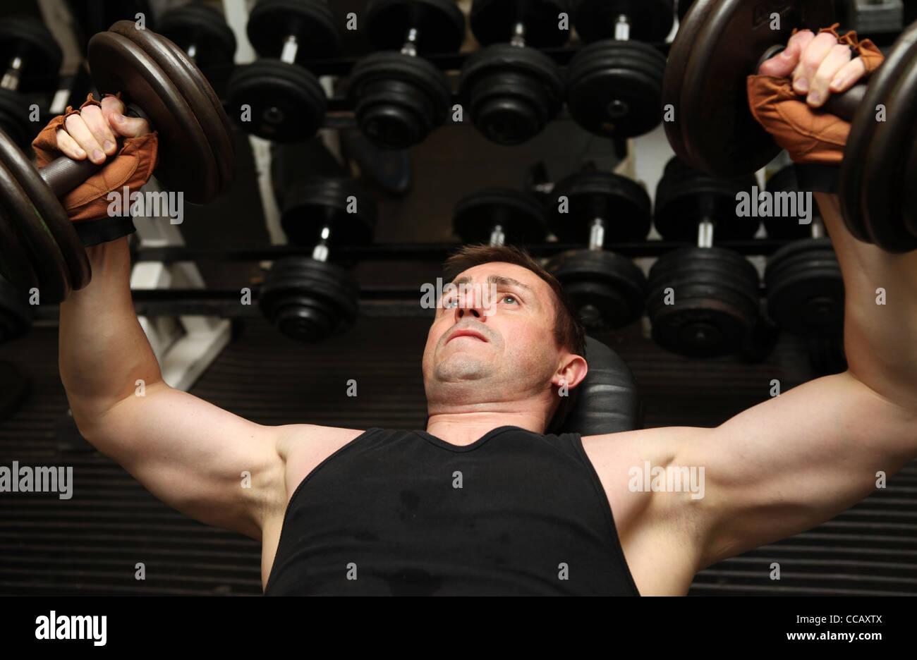 Formación las pesas en el gimnasio. Levantamiento de pesas masculino de fuerza en la parte superior del cuerpo Imagen De Stock