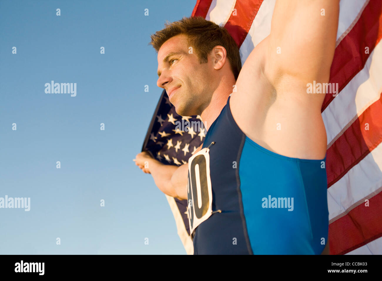 Atleta sosteniendo la bandera americana, vista de ángulo bajo Imagen De Stock