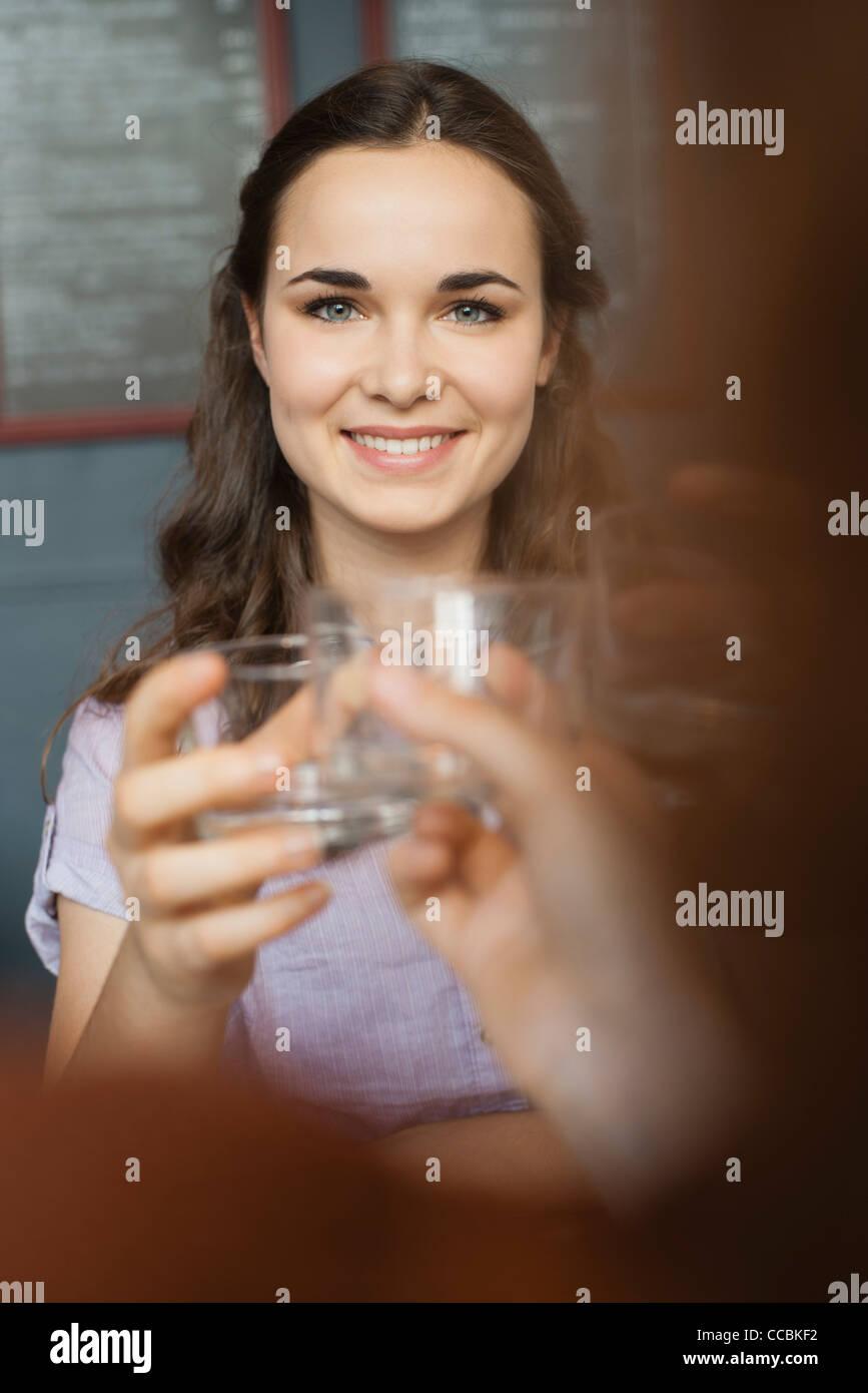 Mujer joven levantando el vidrio con un amigo Foto de stock