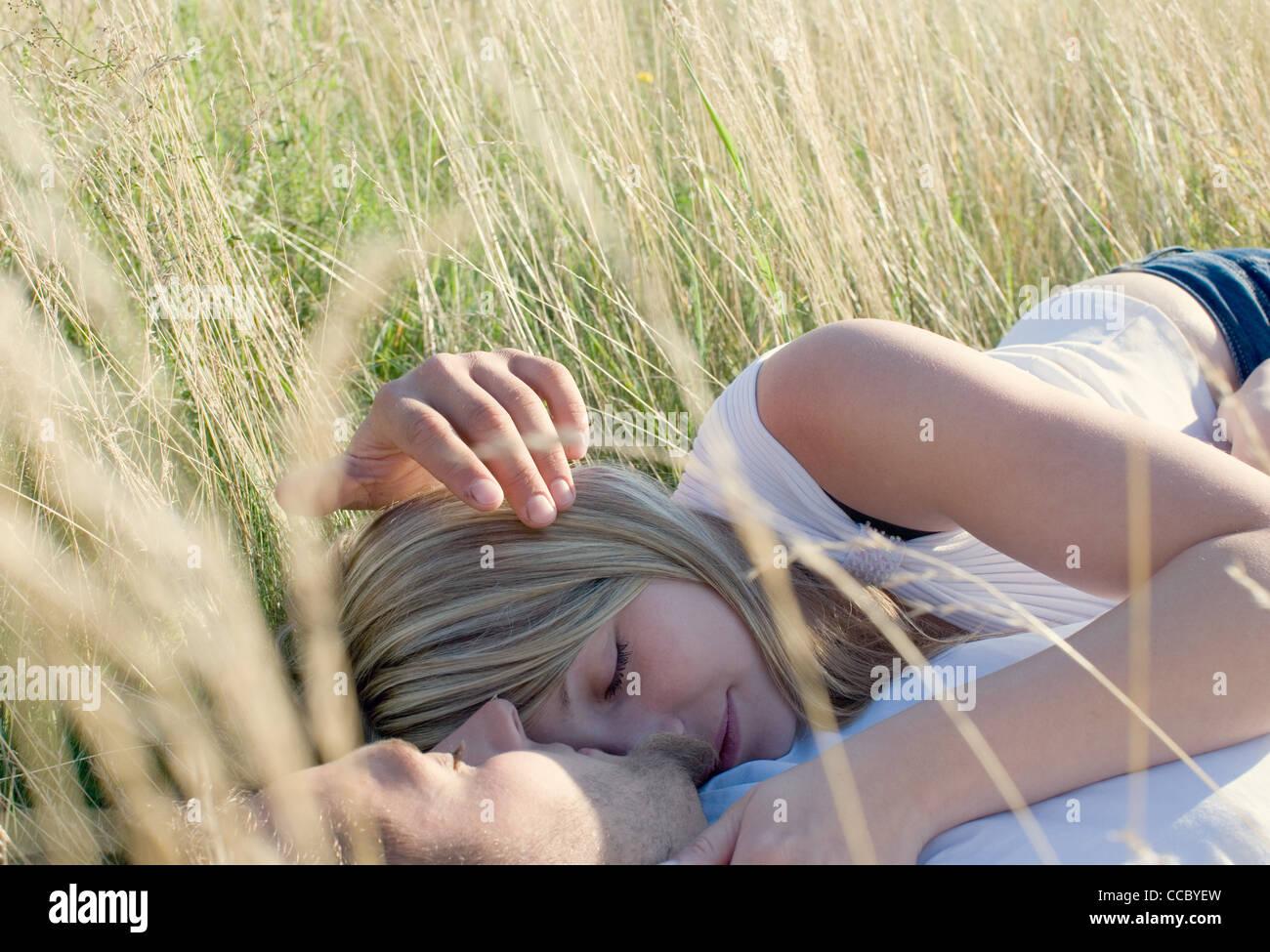 Par yaciendo juntos en el campo de hierba alta Imagen De Stock