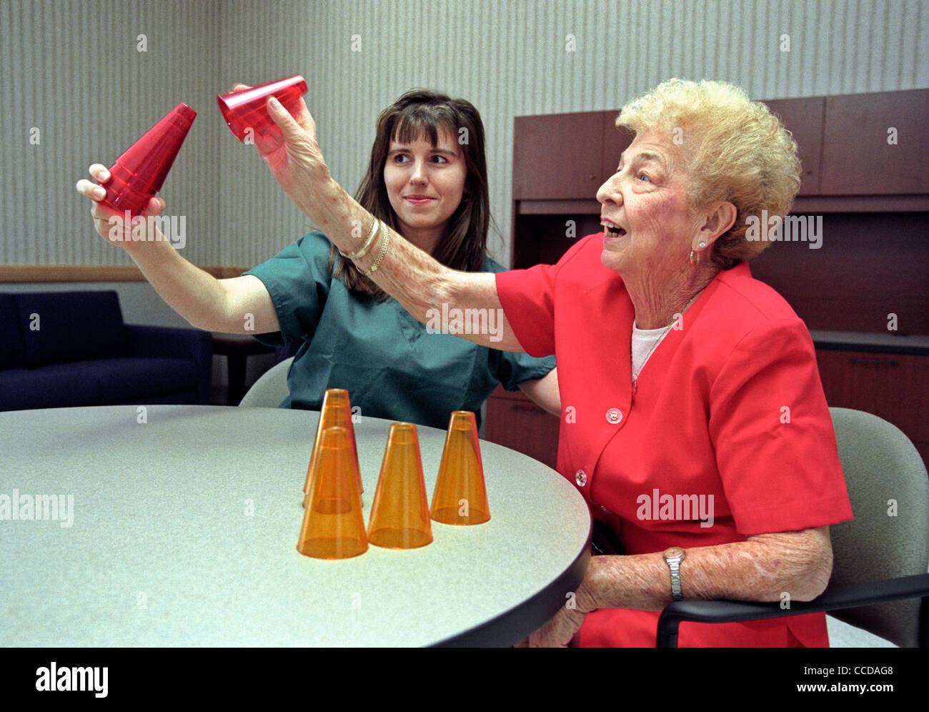 Una mujer jubilada senior en el Departamento Rehabitation del paciente en un hospital recibiendo terapia ocupacional Imagen De Stock