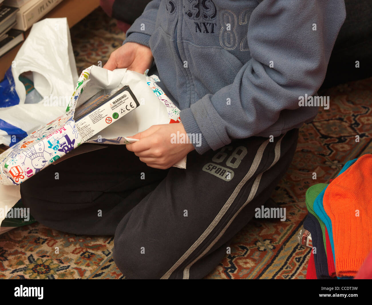 Primer plano de un niño abriendo un regalo de Navidad Imagen De Stock