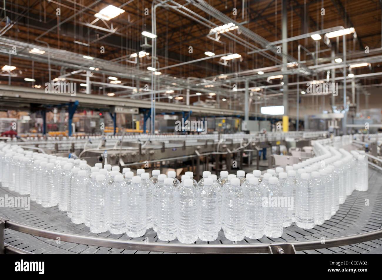 Agua embotellada en transportador en la planta embotelladora Imagen De Stock