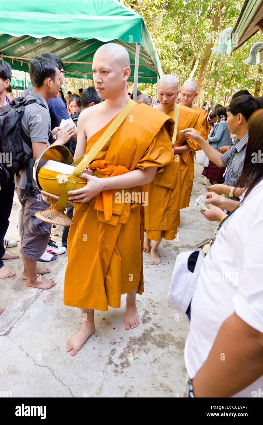 Recién ordenados monjes budistas con las cabezas afeitadas y vistiendo ropas naranjas caminando por la gente poner Foto de stock