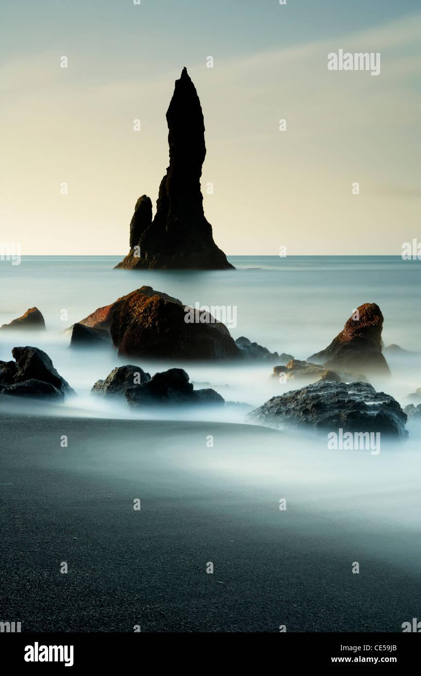 Olas lavando en torno al mar negra volcánica pilas en la costa de Vik en Islandia Foto de stock