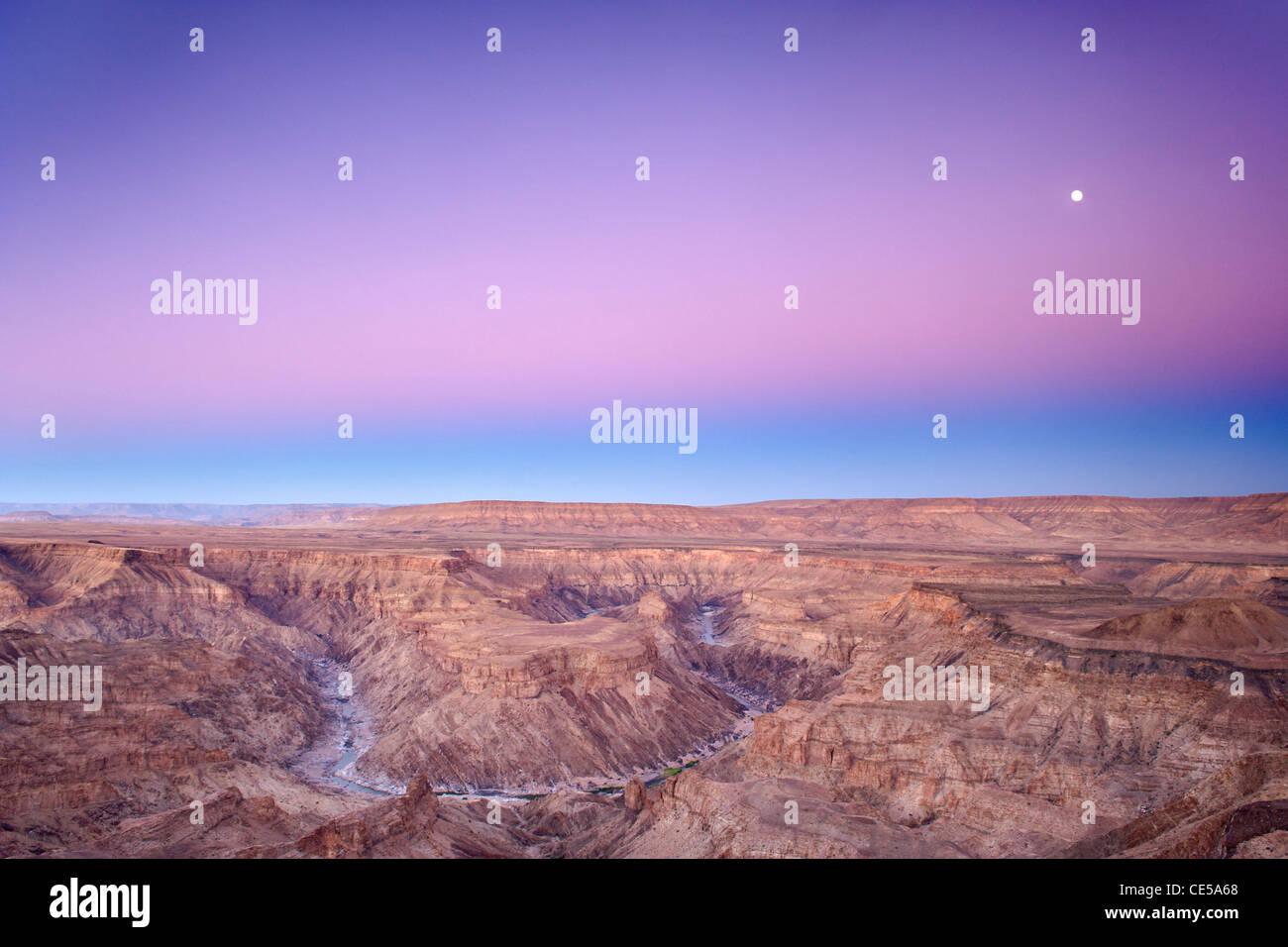Ajuste de la luna llena sobre el cañón del río Fish en el sur de Namibia al amanecer. Imagen De Stock