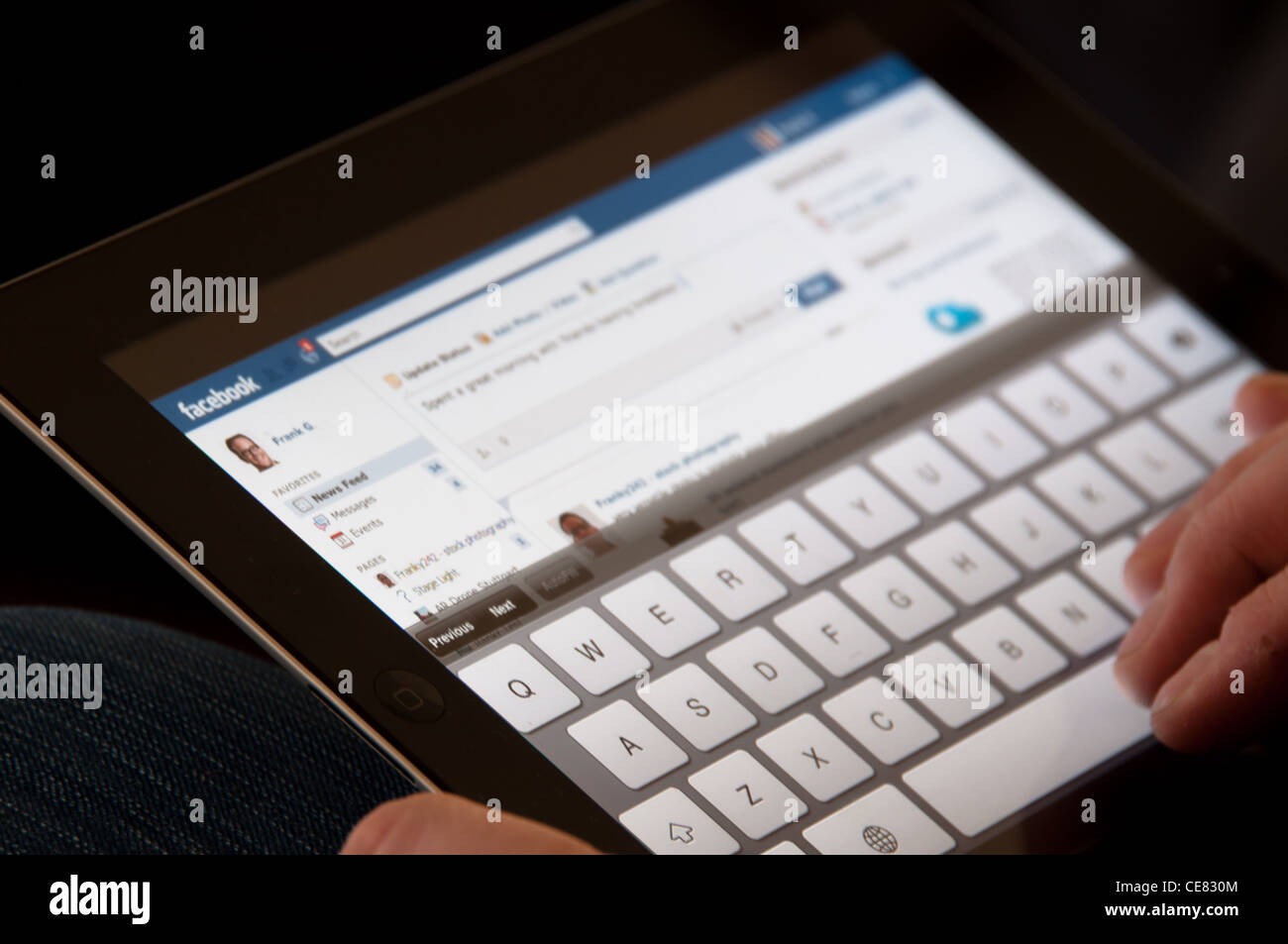 Cerca de un Apple iPad pantalla mostrando el sitio Facebook con dos manos masculinas escribiendo una actualización Imagen De Stock