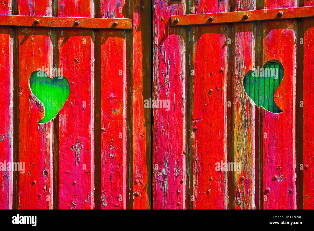 Dos formas de corazón cortadas en una puerta de madera roja, revelando la madera verde detrás, simbólico Imagen De Stock